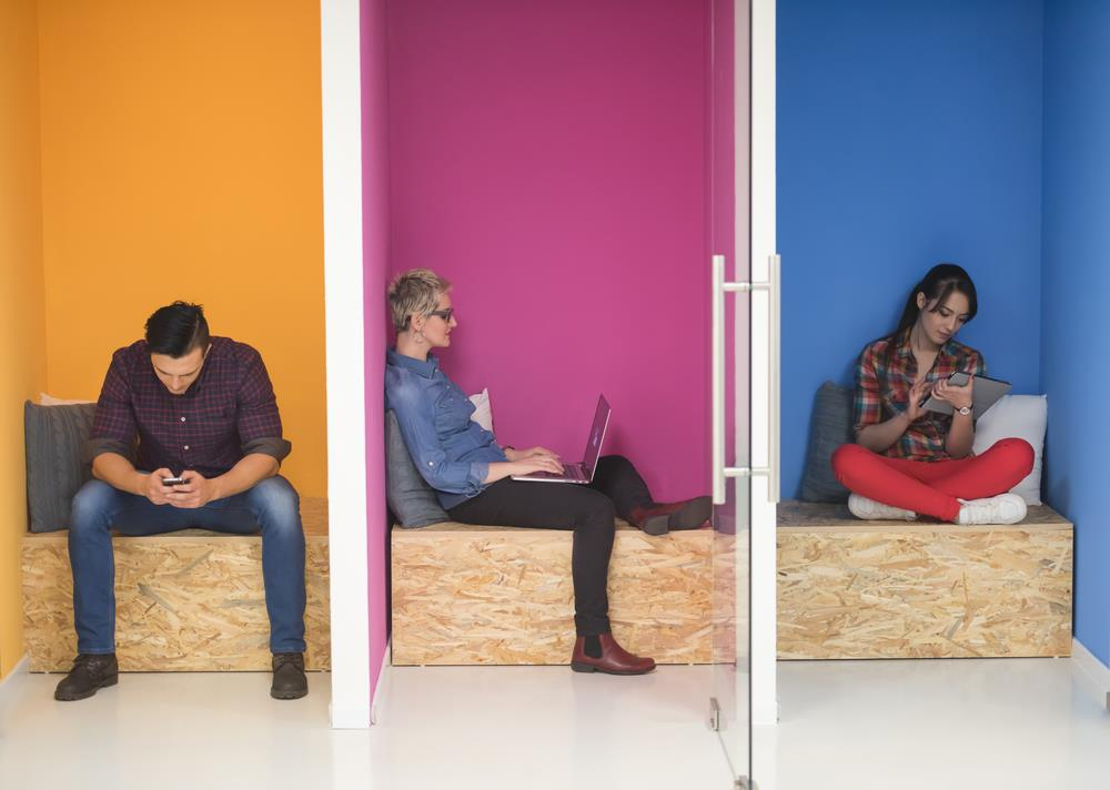 People in colorful phone booths in an office